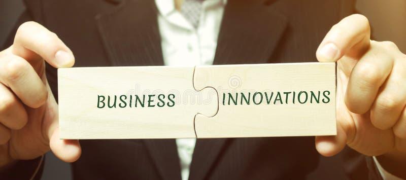 L'homme d'affaires rassemble des puzzles avec les affaires et les innovations de mots Idées innovatrices pour des petites entrepr images libres de droits