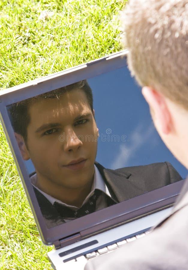 L'homme d'affaires reflecten sur l'ordinateur portatif image libre de droits