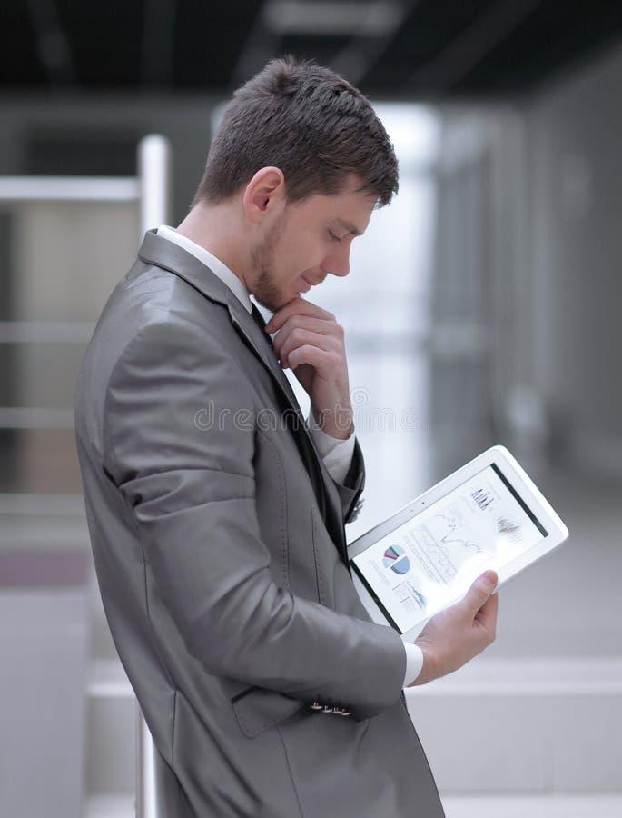 L'homme d'affaires regarde l'écran numérique de comprimé avec le programme numérique image stock