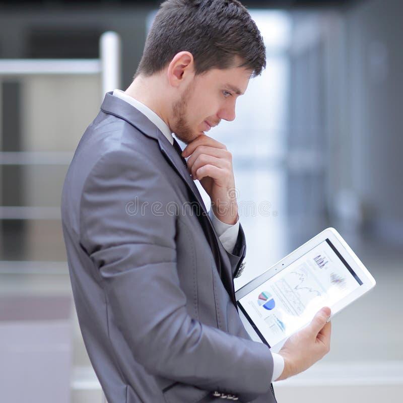 L'homme d'affaires regarde l'écran numérique de comprimé avec le programme numérique images libres de droits
