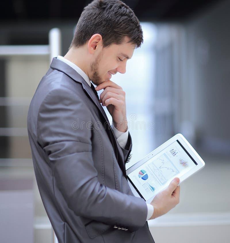 L'homme d'affaires regarde l'écran numérique de comprimé avec le sch numérique images stock