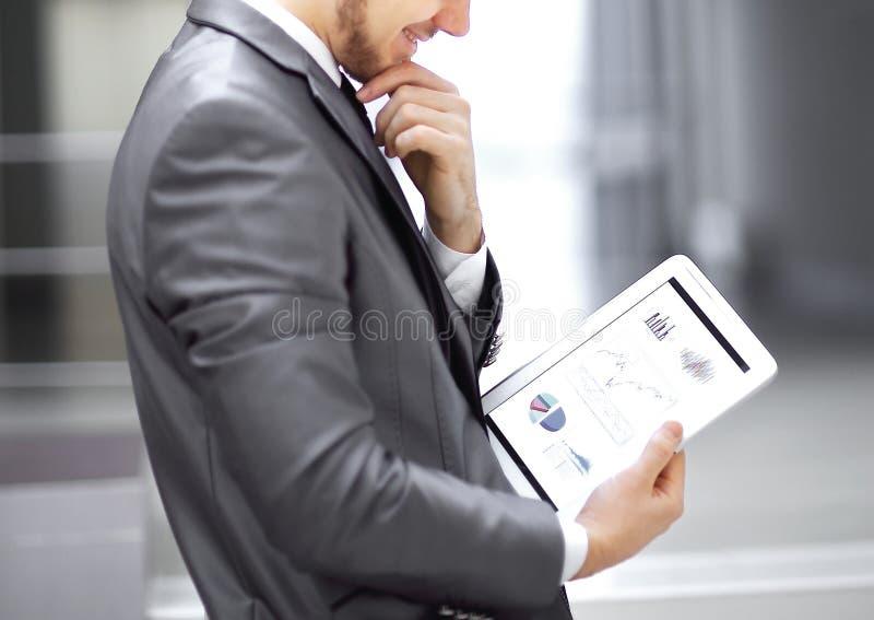 L'homme d'affaires regarde l'?cran num?rique de comprim? avec le programme num?rique photos stock