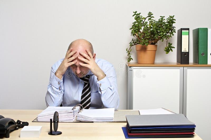 L'homme d'affaires regarde désespérément sur son dossier photo stock
