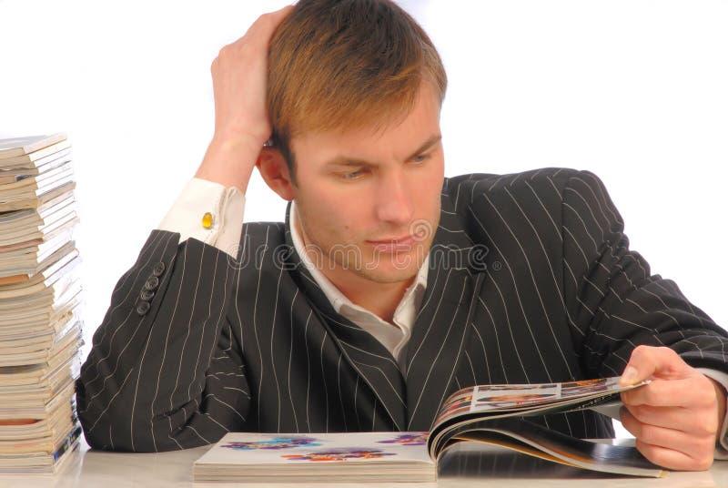 L'homme d'affaires regarde la revue image stock