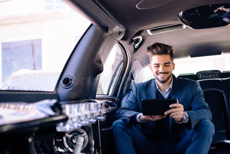 L'homme d'affaires regarde le comprimé et sourit dans la limousine photos stock