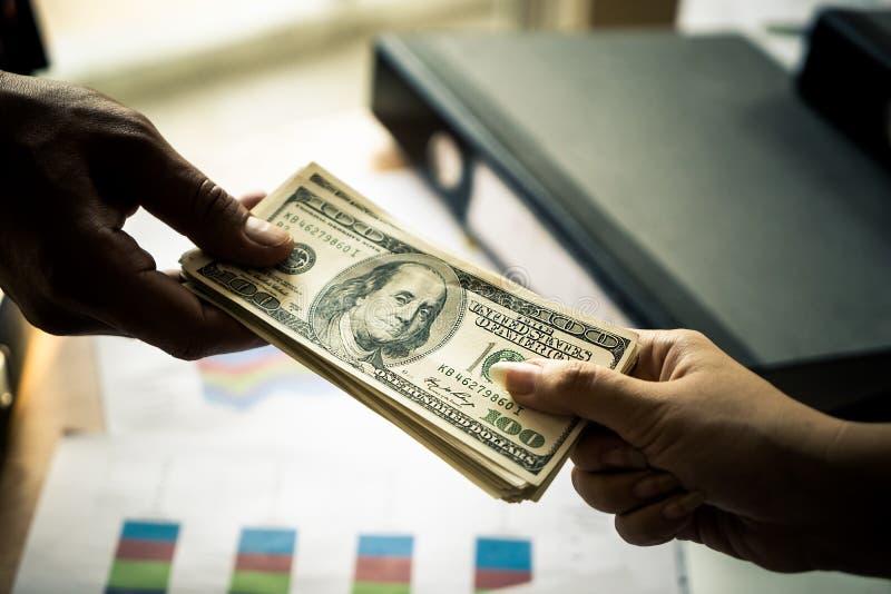 L'homme d'affaires remet l'argent de remise au-dessus de la réunion d'affaires photos stock