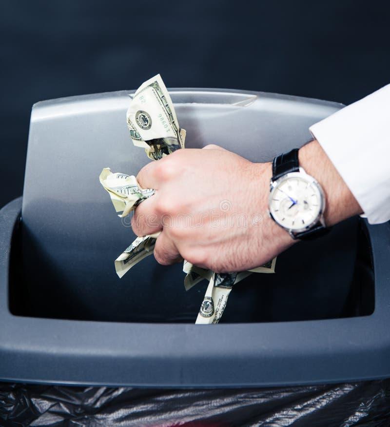 L'homme d'affaires remet les factures de lancement de dollar US dans la poubelle image stock