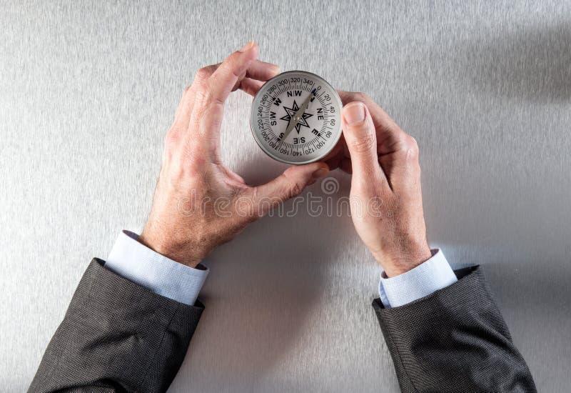 L'homme d'affaires remet rechercher sa manière d'entreprise en avant avec une boussole photographie stock