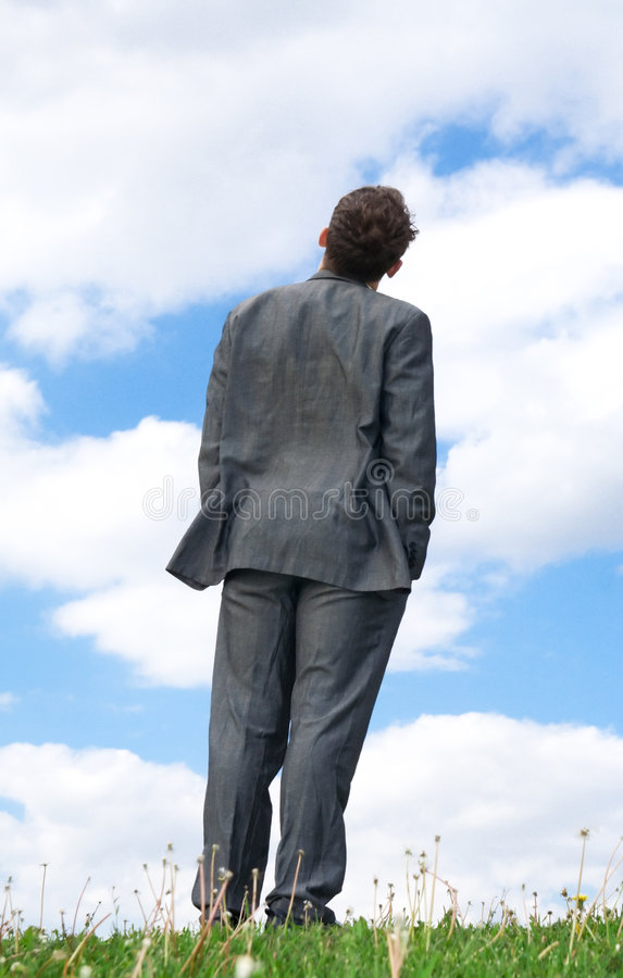 L'homme d'affaires restant sur une herbe verte images libres de droits