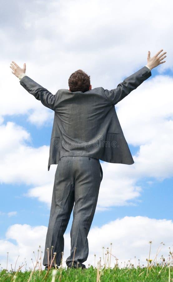L'homme d'affaires restant sur une herbe verte image libre de droits