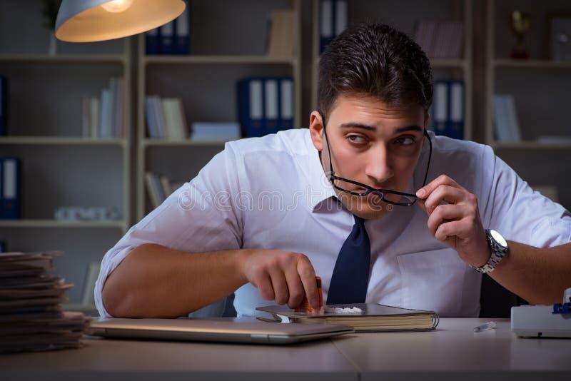 L'homme d'affaires restant tard dans le bureau pour des drogues image stock