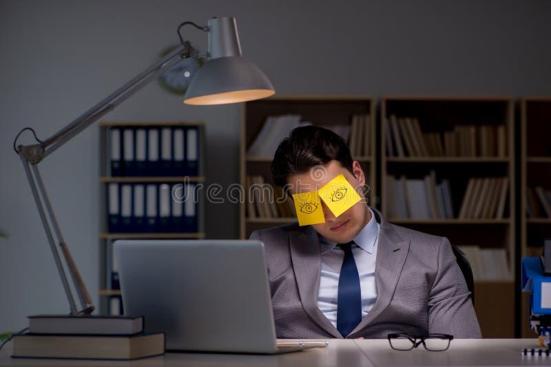 L'homme d'affaires restant tard pour trier des priorités photographie stock