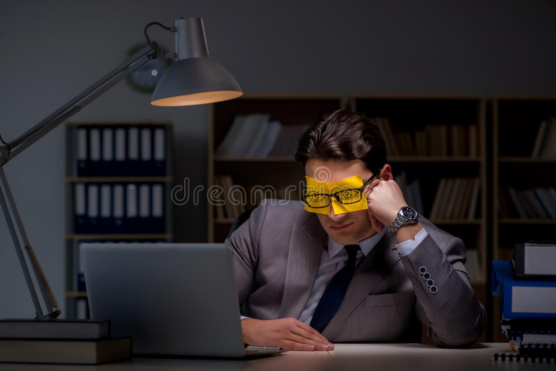 L'homme d'affaires restant tard pour trier des priorités photo libre de droits