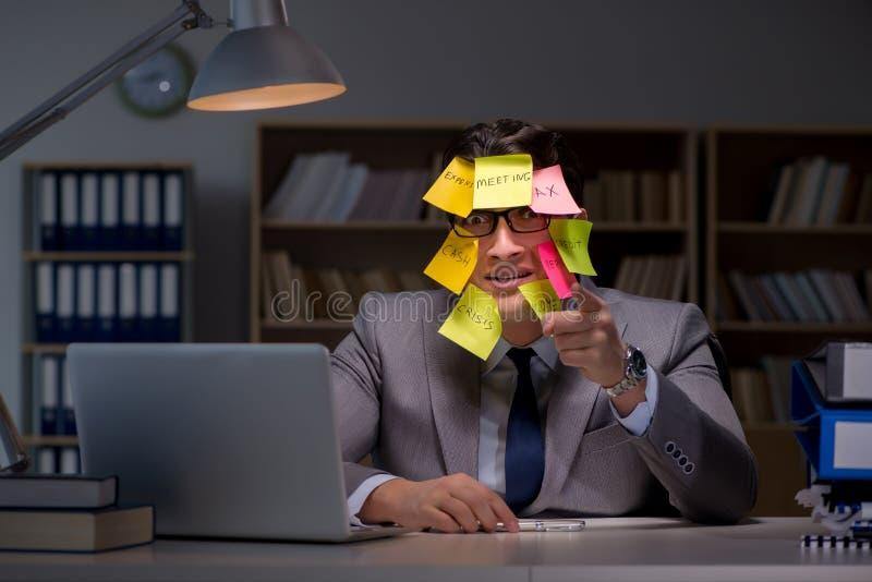 L'homme d'affaires restant tard pour trier des priorités images stock