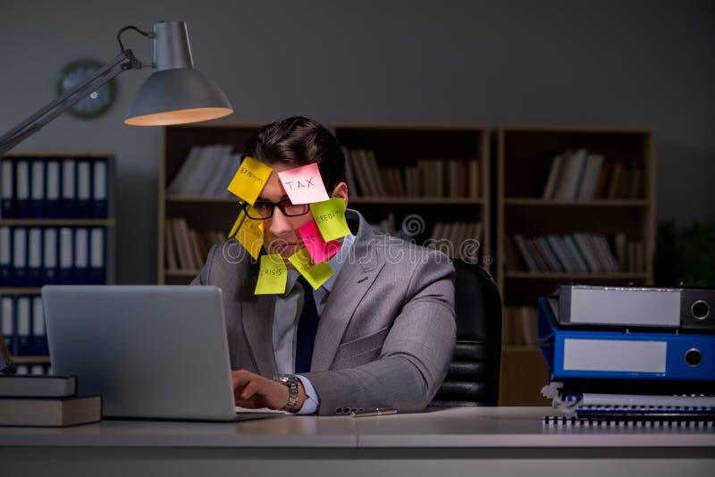L'homme d'affaires restant tard pour trier des priorités photo stock