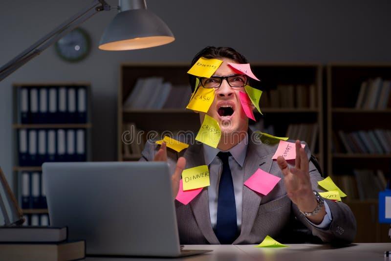 L'homme d'affaires restant tard pour trier des priorités image stock