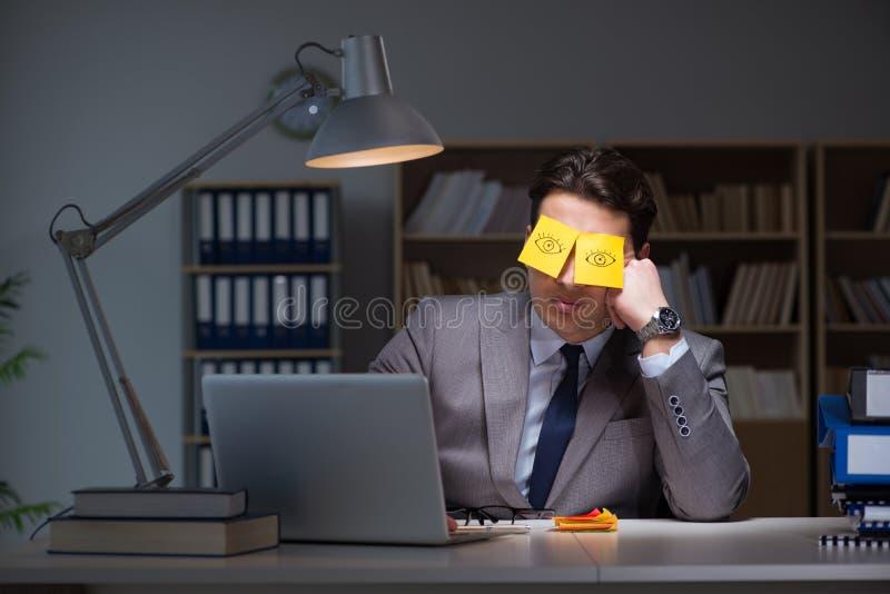L'homme d'affaires restant tard pour trier des priorités image libre de droits