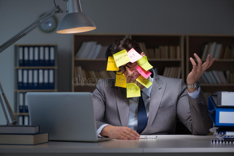 L'homme d'affaires restant tard pour trier des priorités photographie stock libre de droits