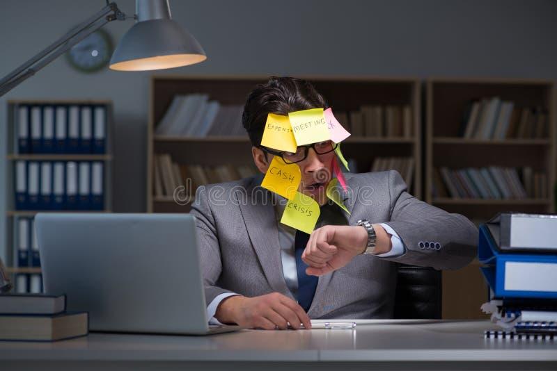 L'homme d'affaires restant tard pour trier des priorités images libres de droits