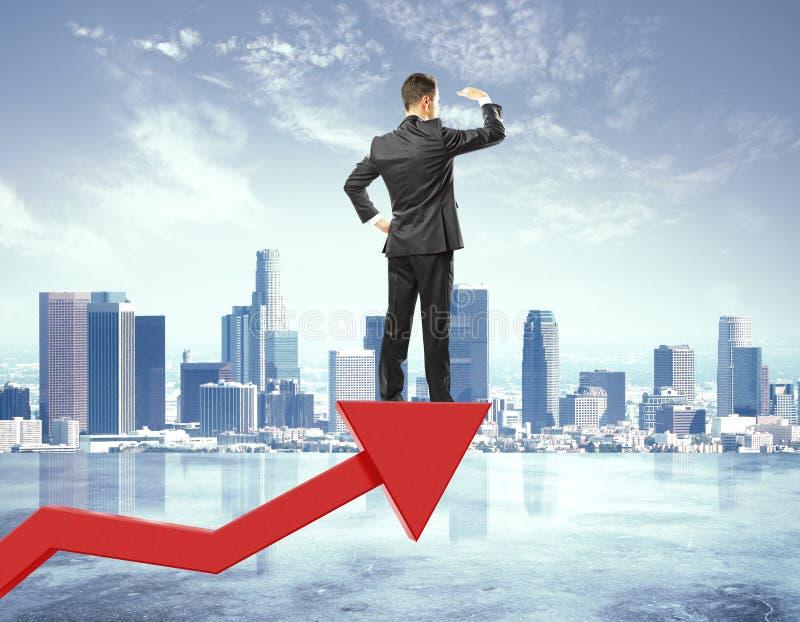L'homme d'affaires reste sur la flèche rouge du graphique de gestion et de l'I de regard photos stock