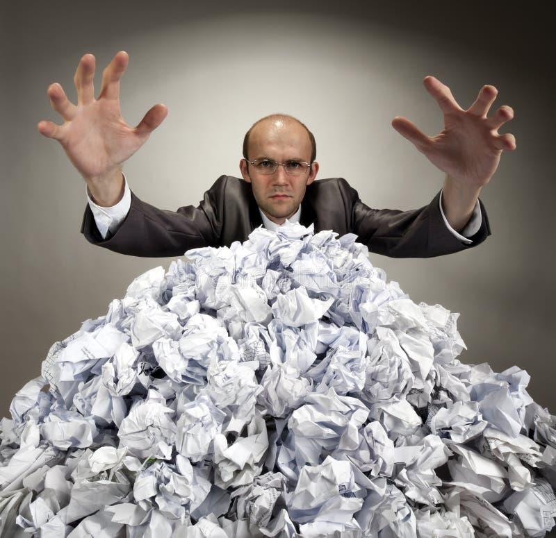 L'homme d'affaires sérieux atteint à l'extérieur des papiers photos stock