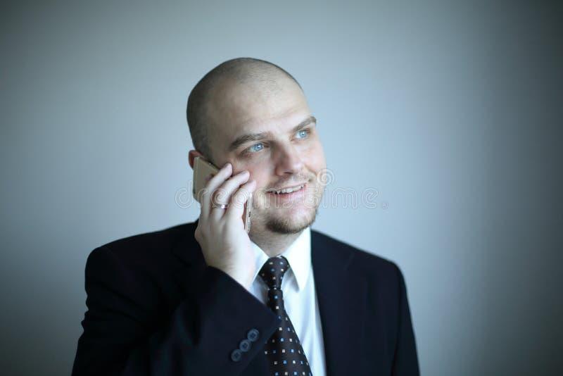 L'homme d'affaires sûr dans un lien écoute l'interlocuteur au téléphone photos stock