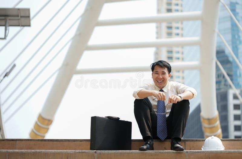 L'homme d'affaires s'asseyent heureusement riant du passage couvert moderne d'échelle images stock