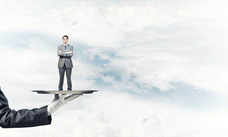 L'homme d'affaires sûr s'est présenté sur le plateau en métal sur le fond de ciel bleu photo libre de droits