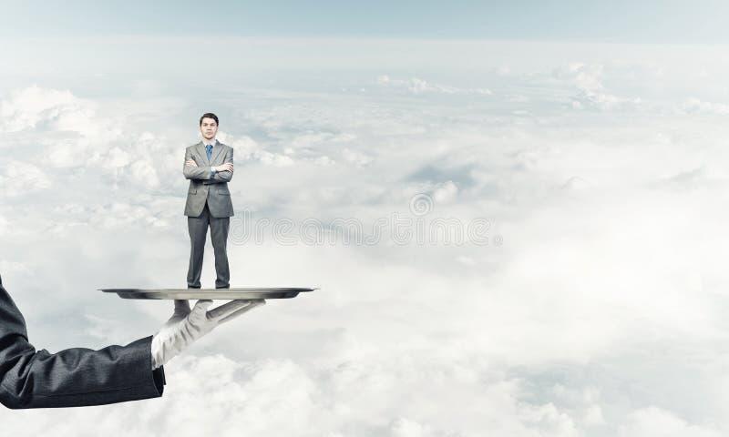 L'homme d'affaires sûr s'est présenté sur le plateau en métal sur le fond de ciel bleu image stock
