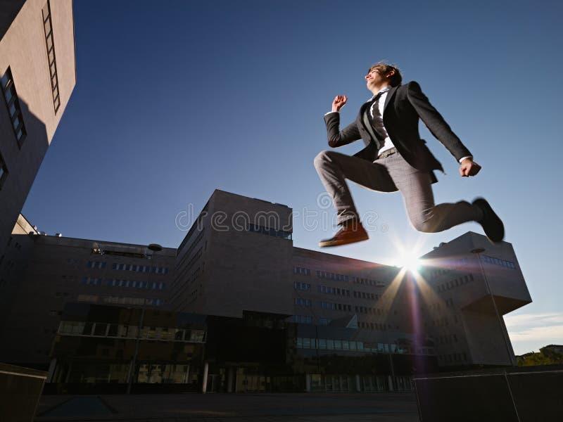 L'homme d'affaires sautant et souriant en dehors du bureau image stock