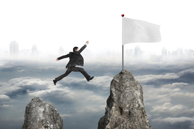 L'homme d'affaires sautant par-dessus la crête de montagne pour diminuer avec les citys nuageux images libres de droits