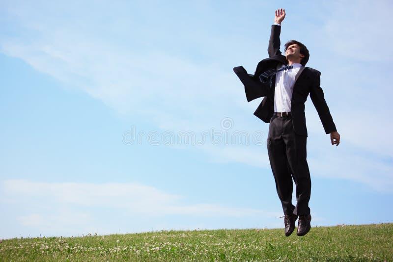 L'homme d'affaires sautant sur l'herbe images stock