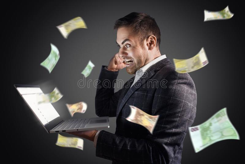 L'homme d'affaires se réjouit au vol d'argent d'un ordinateur portable Revenus en ligne de concept, jeu, indépendant photographie stock libre de droits