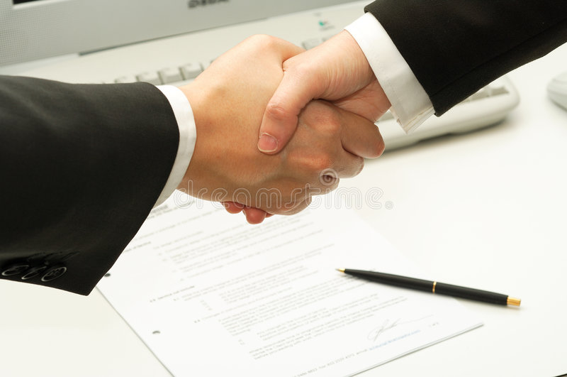 L'homme d'affaires se serrent la main après la signature d'un contrat image libre de droits