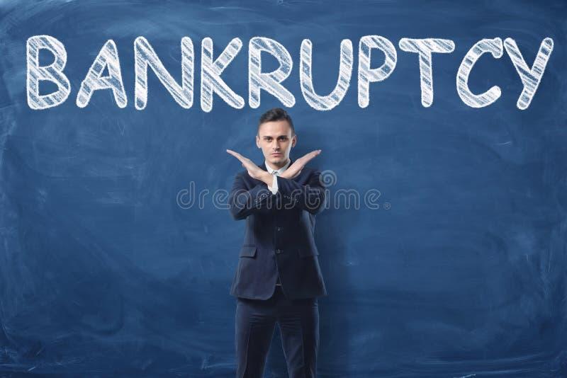 L'homme d'affaires se tenant avec ses mains aiment le signe croisé et expriment le ` de faillite de ` écrit sur le tableau noir d photos libres de droits