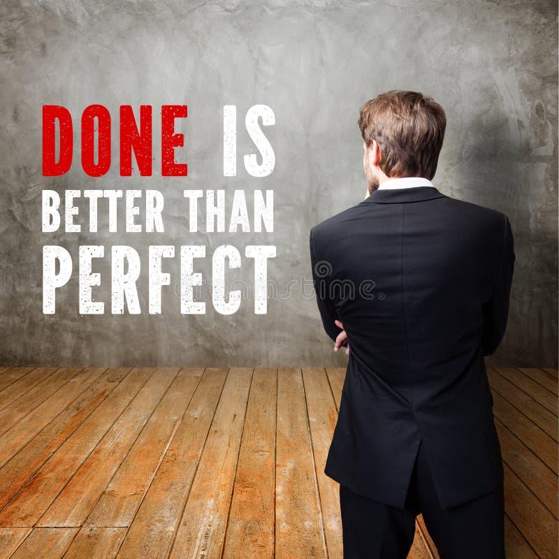 L'homme d'affaires se tenant devant un mur avec le ` de message fait est meilleur que parfait le ` photographie stock libre de droits