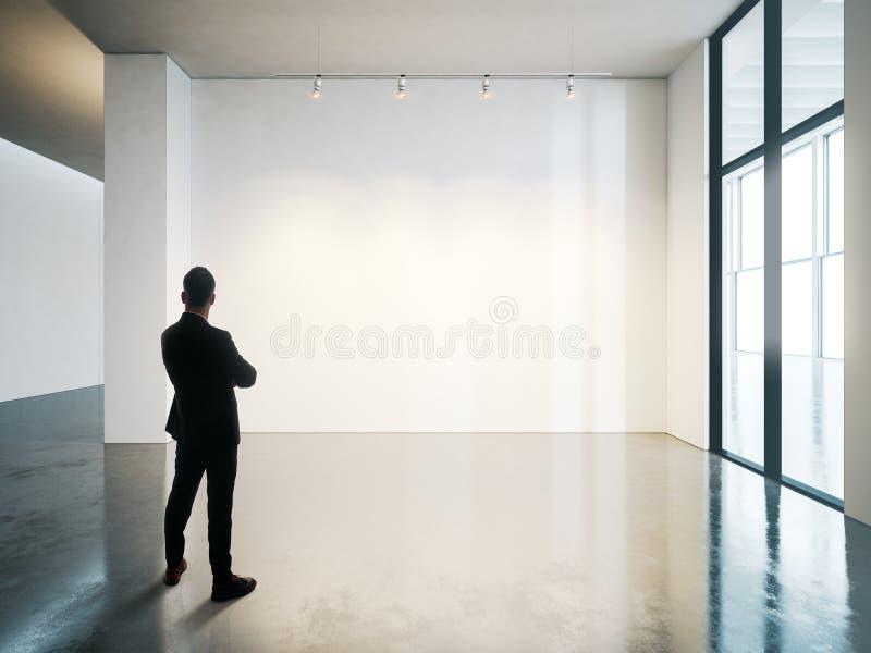 L'homme d'affaires se tient dans l'intérieur blanc vide de musée avec le plancher en béton horizontal photos stock