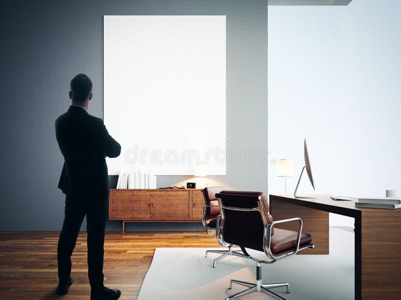L'homme d'affaires se tient dans le bureau moderne avec la toile blanche vide photographie stock libre de droits