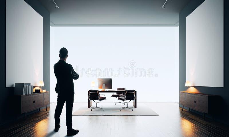 L'homme d'affaires se tient dans le bureau moderne avec la toile deux vide couleur photo libre de droits