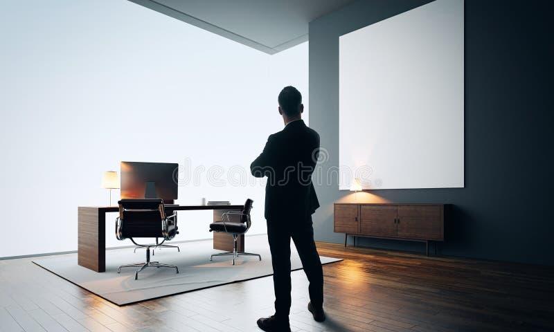 L'homme d'affaires se tient dans le bureau moderne avec la toile vide couleur images libres de droits