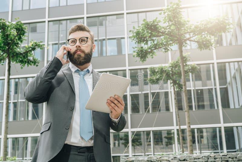 L'homme d'affaires se tient extérieur, tient la tablette et parle à son téléphone portable Équipez fonctionner Conversation d'aff photos libres de droits