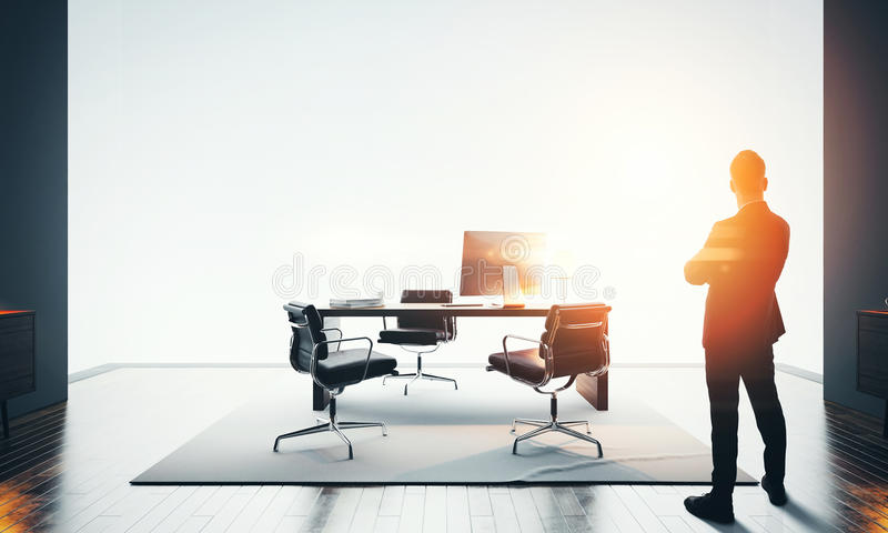 L'homme d'affaires se tient le bureau moderne et en regardant l'horizon Effets de Bokeh images stock