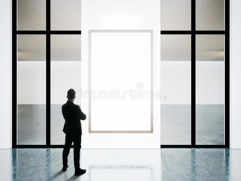 L'homme d'affaires se tient vis-à-vis des cadres vides dans la galerie contemporaine photo libre de droits