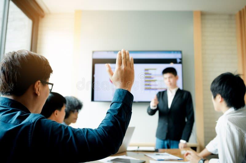 L'homme d'affaires soulevant la main veut demander quelque chose dans la salle de réunion photos stock