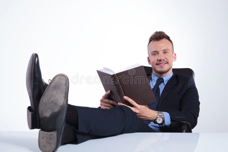 L'homme d'affaires sourit avec le livre ouvert photographie stock