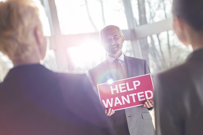 L'homme d'affaires supérieur de sourire montrant l'aide a voulu le signe aux femmes d'affaires tout en se tenant au bureau photo stock