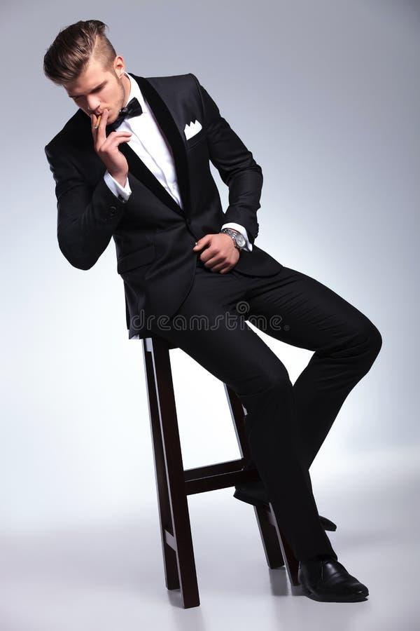 L'homme d'affaires sur la chaise fume et regarde vers le bas images libres de droits