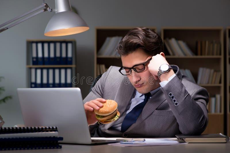 L'homme d'affaires tard la nuit mangeant un hamburger photo libre de droits