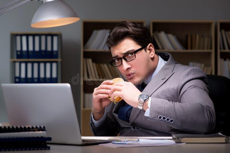 L'homme d'affaires tard la nuit mangeant un hamburger photos libres de droits