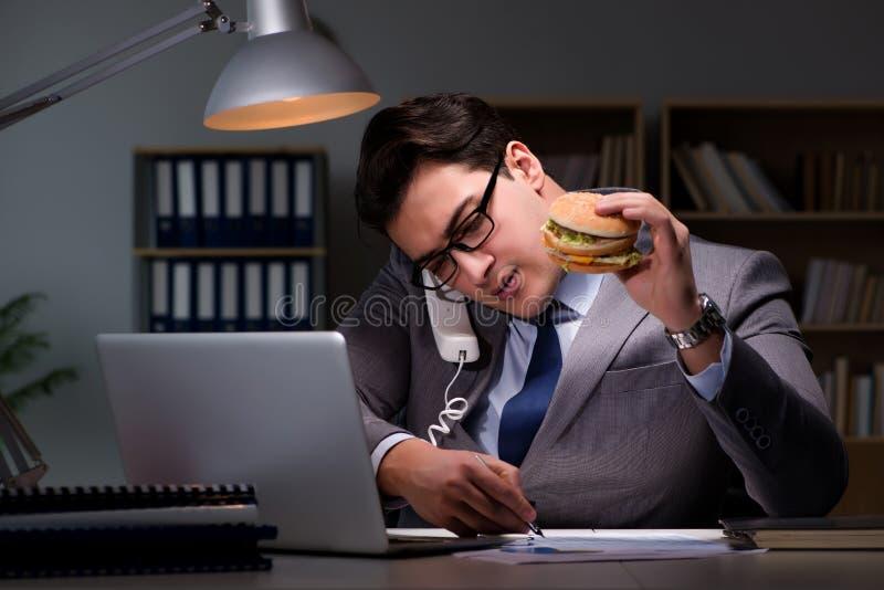 L'homme d'affaires tard la nuit mangeant un hamburger photographie stock libre de droits